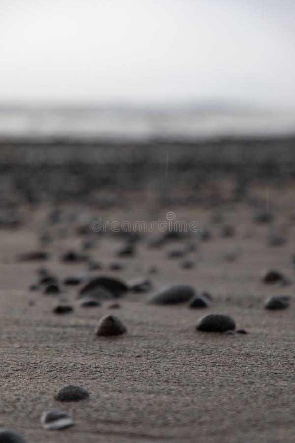 Feche acima da areia vulcânica da praia com as rochas em Bali, Indonésia imagem de stock