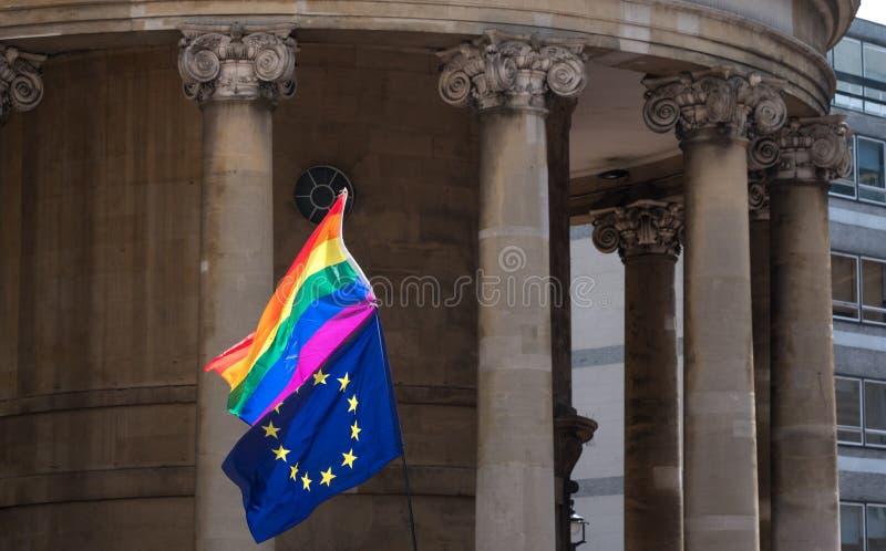 Feche acima da bandeira do arco-íris LGBT e da bandeira da UE que voam junto em Pride Parade alegre em Londres 2018 fotografia de stock royalty free