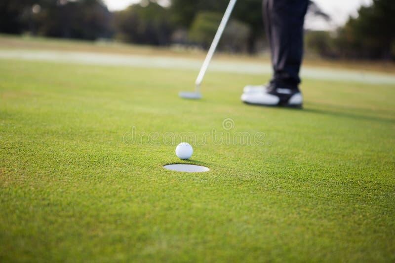 Feche acima da bola de golfe e de um furo imagens de stock royalty free