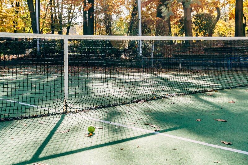 Feche acima da bola de tênis ao lado do campo de tênis vazio fotografia de stock royalty free