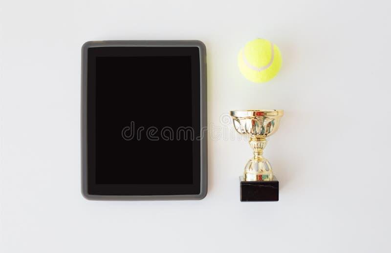 Feche acima da bola de tênis, do copo e do PC da tabuleta foto de stock