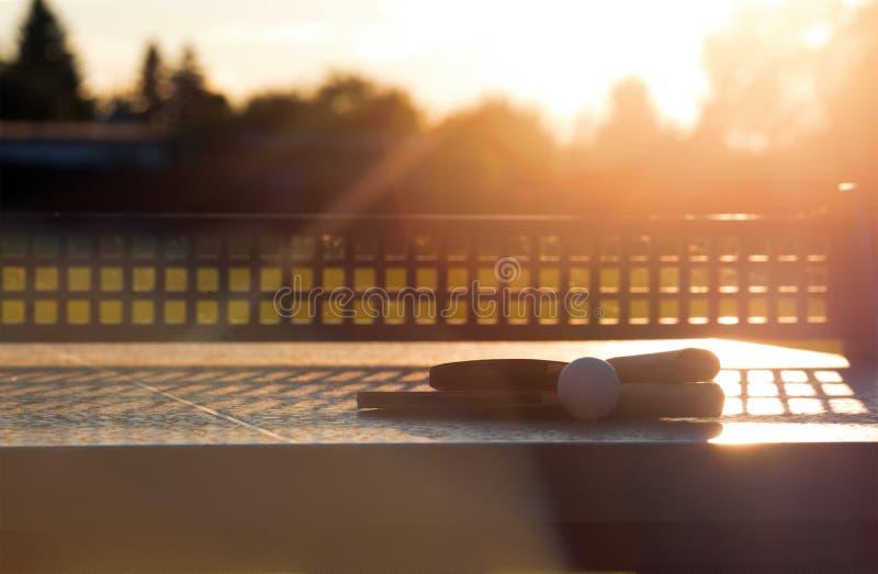 Feche acima da bola de tênis de mesa com as raquetes de tênis na tabela de pedra em luzes ensolaradas, equipamento do tênis para  fotos de stock
