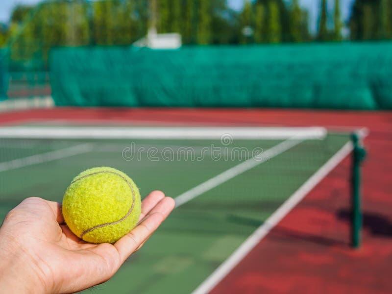 Feche acima da bola de tênis na mão no campo de tênis Ostente a fotografia de stock