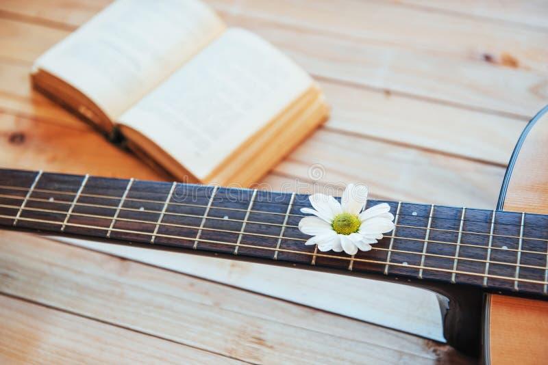 Feche acima da cabeça clássica da guitarra com vidros e livro imagens de stock