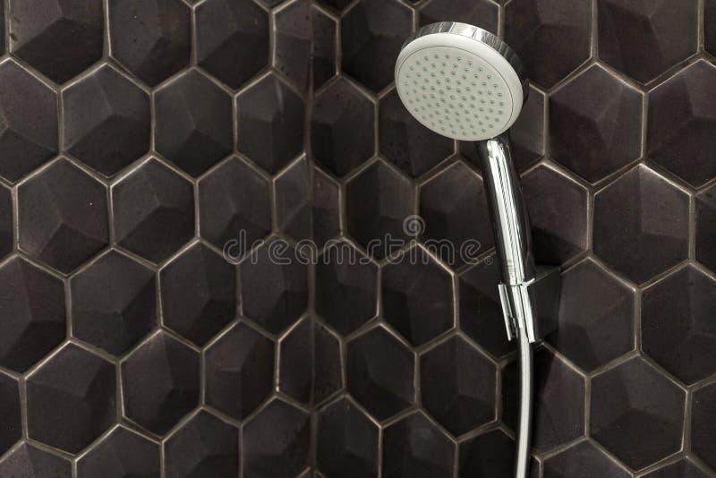 Feche acima da cabeça de chuveiro nova da chuva no banheiro contra um fundo de telhas pretas fotos de stock royalty free