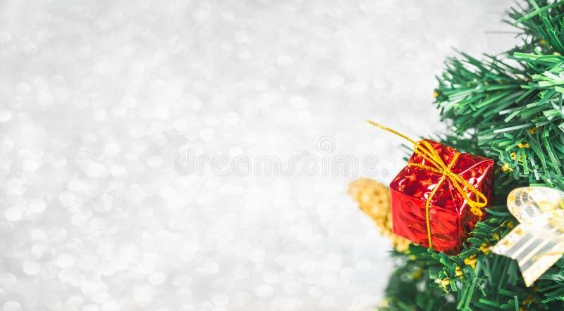 Feche acima da caixa de presente vermelha na árvore de Natal verde no lig branco do bokeh fotos de stock royalty free