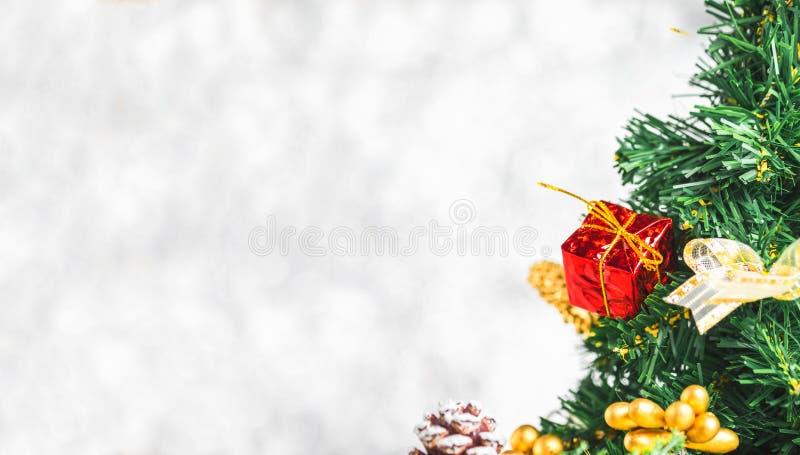 Feche acima da caixa de presente vermelha na árvore de Natal verde no lig branco do bokeh foto de stock royalty free