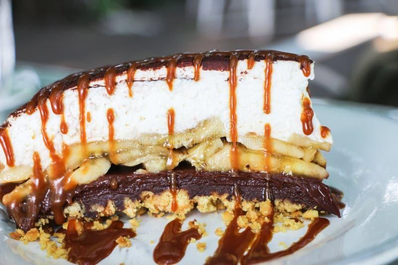 Feche acima da camada de bolo do banoffee com o caramelo que toping no pla branco fotos de stock