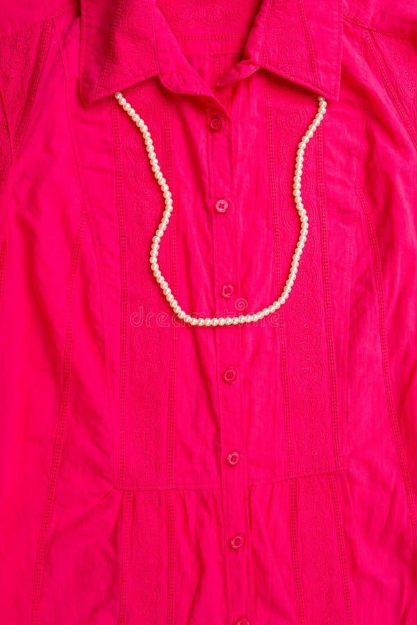 Feche acima da camisa fêmea cor-de-rosa com grânulos da colar imagens de stock royalty free