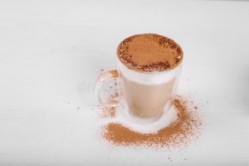 Feche acima da canela do latte polvilham no fundo branco foto de stock