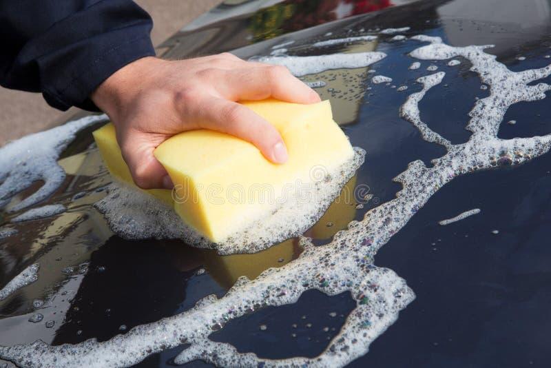 Feche acima da capota de lavagem do carro da mão usando a esponja foto de stock