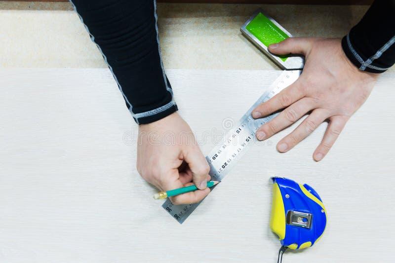 Feche acima da carpintaria, equipe a mão usando a fita métrica medir a prancha de madeira e marcando a com lápis Vista de acima fotografia de stock royalty free