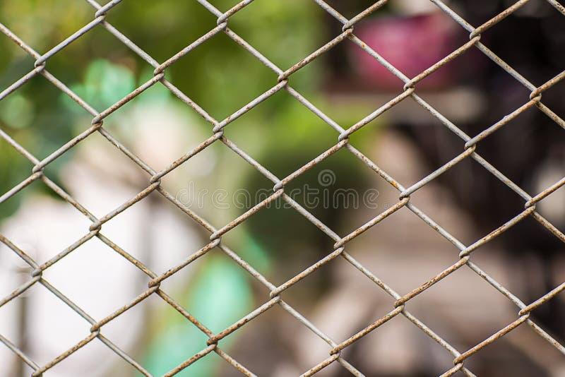 Feche acima da cerca Chain Engranzamento do metal Cerca suja com fundo borrado foto de stock royalty free