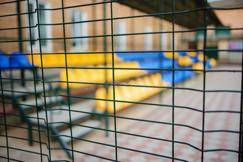 Feche acima da cerca rede-dada forma metálica do fio em um fundo de assentos azuis e amarelos vazios dos esportes do suporte gran fotos de stock royalty free