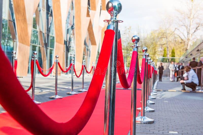 Feche acima da cerimônia do tapete vermelho com foco seletivo nos postes e nas cordas com convidados e fundo borrados do fotógraf fotografia de stock