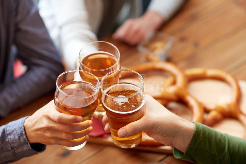 Feche acima da cerveja do tinido das mãos na barra ou no bar fotografia de stock
