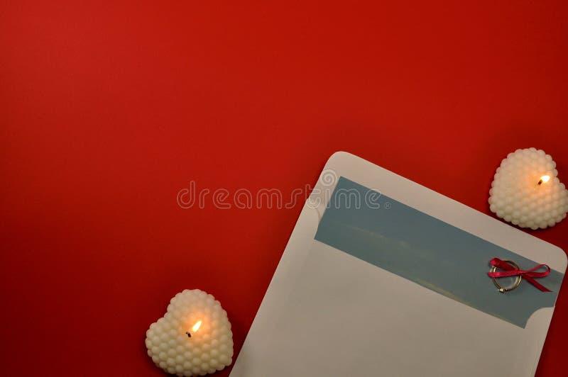 Feche acima da configuração do plano do coração e do envelope brancos de queimadura da vela com letra e do anel de diamante no fu foto de stock