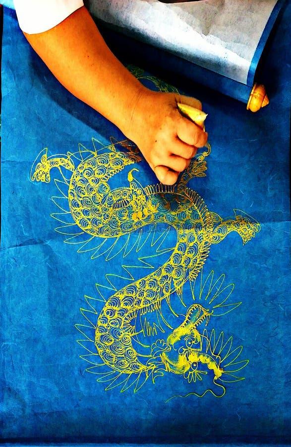 Feche acima da cor acrílica com pintura do dragão no papel azul da amoreira fotos de stock