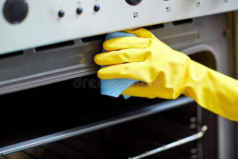 Feche acima da cozinha do forno da limpeza da mulher em casa fotografia de stock