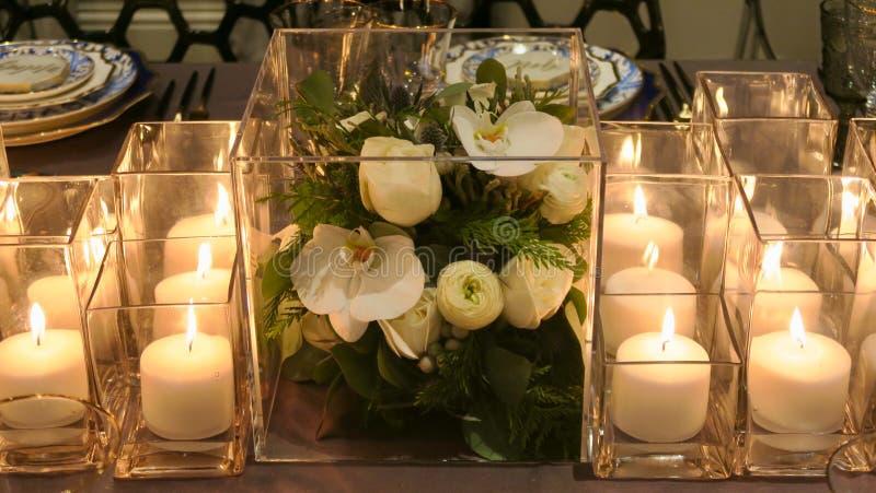 Feche acima da decoração e das velas da flor na tabela de jantar foto de stock