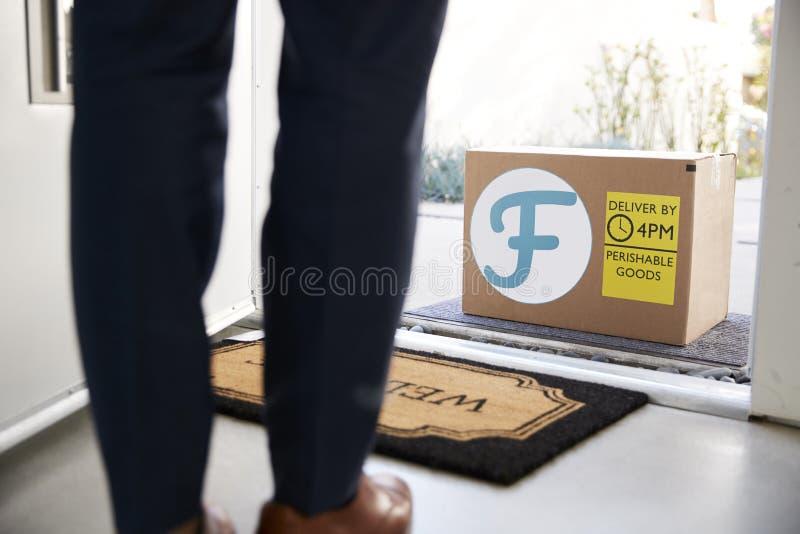 Feche acima da entrega a domicílio de Front Door To Fresh Food da abertura do homem na caixa de cartão fora de Front Door fotografia de stock