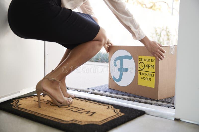 Feche acima da entrega a domicílio de Front Door To Fresh Food da abertura da mulher na caixa de cartão fora de Front Door imagens de stock royalty free