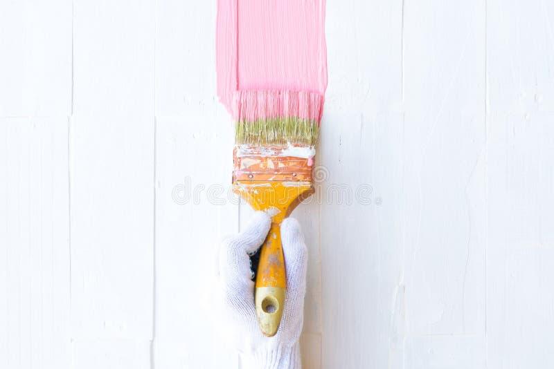 Feche acima da escova da terra arrendada da mão da mulher que pinta a cor cor-de-rosa fotografia de stock royalty free