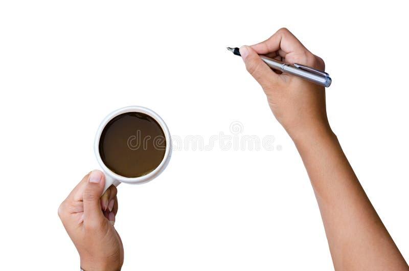 Feche acima da escrita do braço das mulheres com pena metálica na mão branca do fundo que guarda uma pena no copo de café branco  imagens de stock royalty free