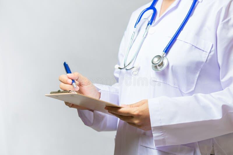 Feche acima da escrita fêmea do doutor da medicina na prancheta Medica imagens de stock royalty free