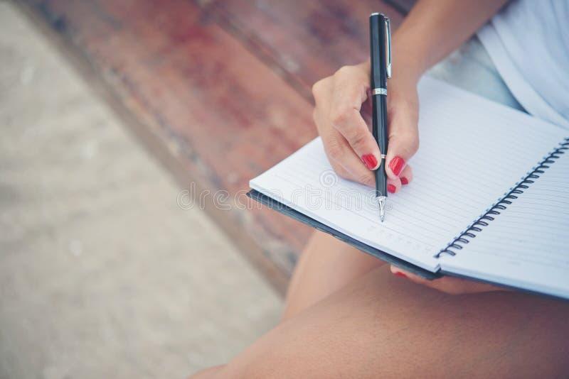 Feche acima da escrita da mão da mulher no bloco de notas foto de stock