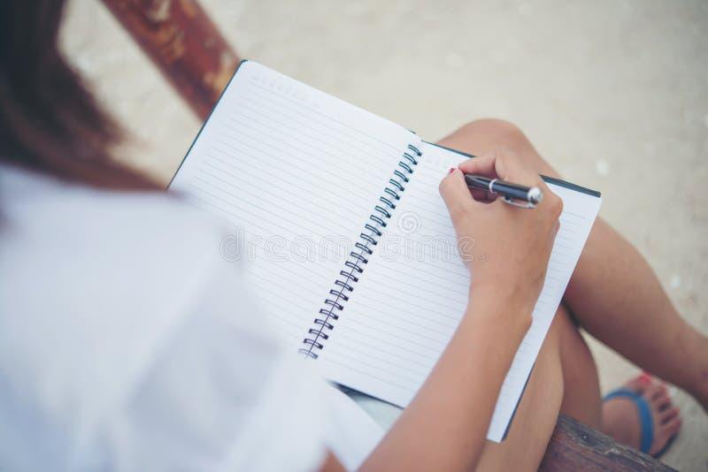 Feche acima da escrita da mão da mulher no bloco de notas foto de stock royalty free