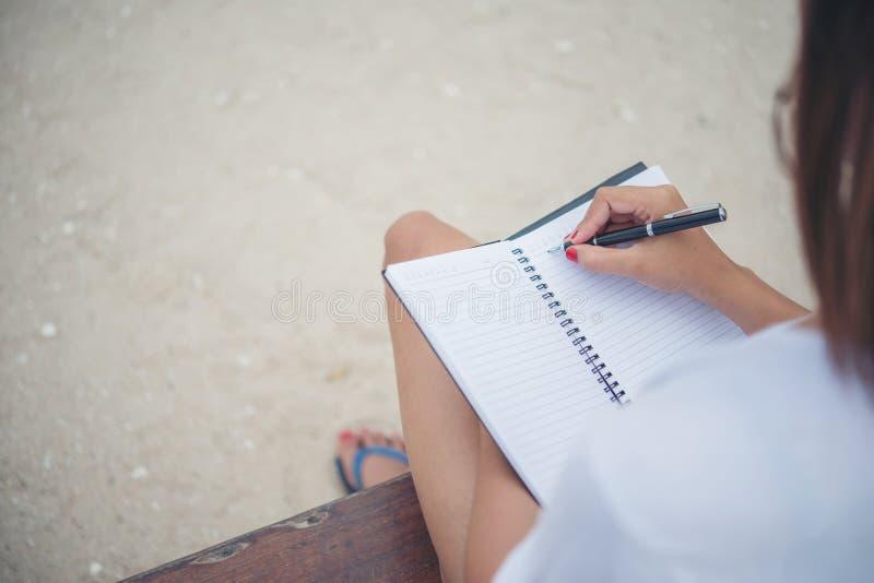 Feche acima da escrita da mão da mulher no bloco de notas fotos de stock