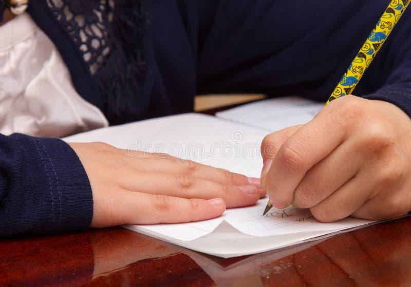 Feche acima da escrita no papel, matemática desarrumado da mão do ` s da criança da escrita na tabela de madeira na sala, pena de imagem de stock royalty free