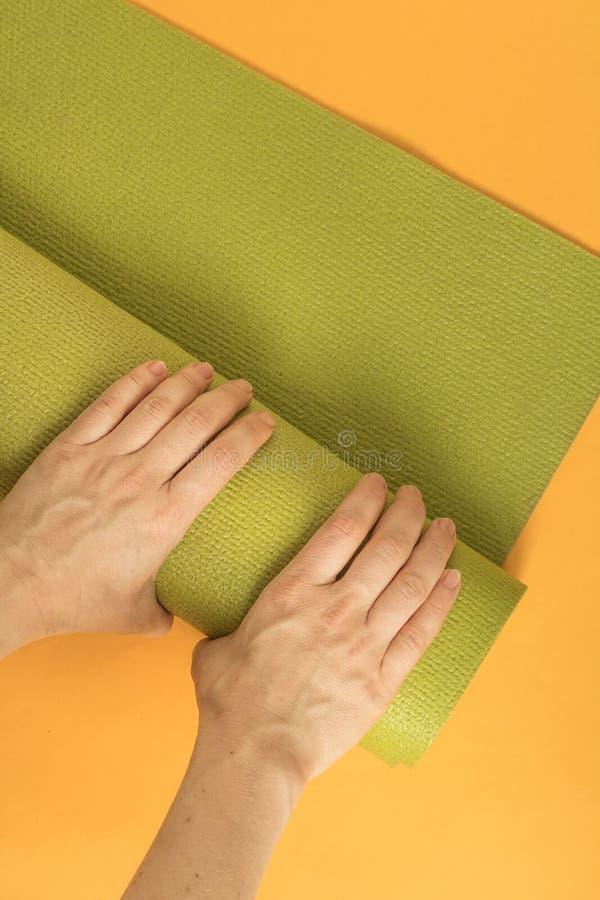 Feche acima da esteira de borracha da dobra fêmea do iogue após ter praticado a ioga fotos de stock