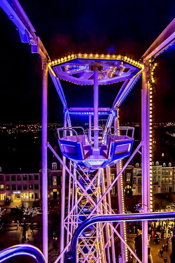 Feche acima da estrutura do metal da roda da fortuna com uma combinação de luzes amarelas azuis roxas do en imagens de stock