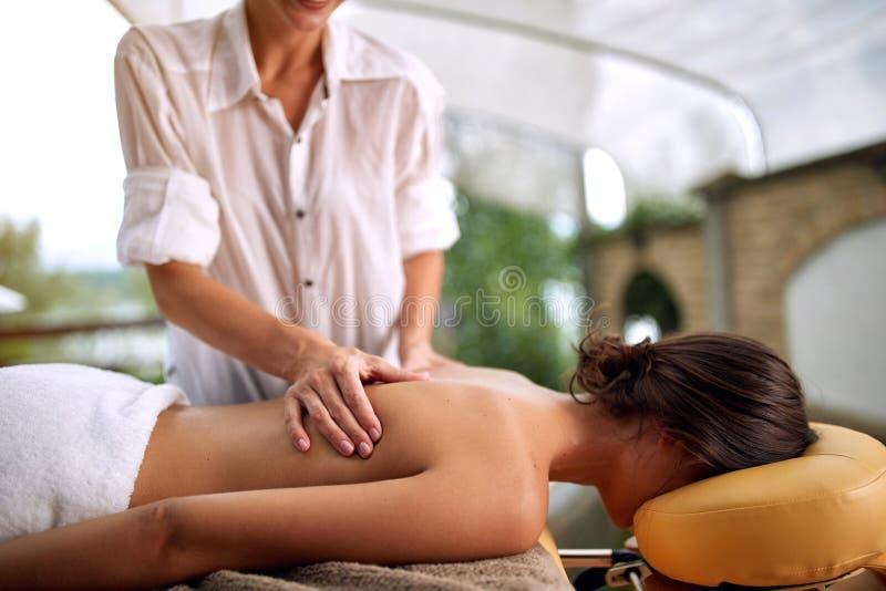 Feche acima da fêmea que recebe a massagem traseira em termas do salão de beleza imagens de stock royalty free