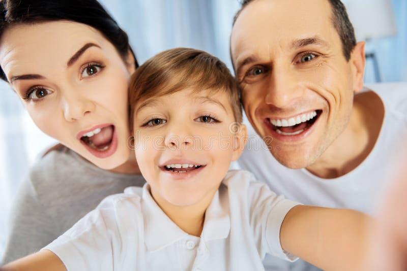 Feche acima da família alegre engraçada que toma o selfie imagens de stock royalty free