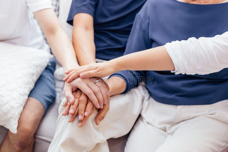Feche acima da família com crianças adultas e os pais superiores que põem as mãos que sentam-se junto no sofá em casa junto Unida fotografia de stock