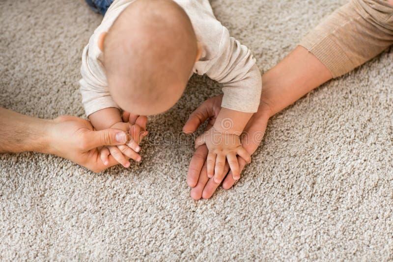 Feche acima da família com o bebê no tapete foto de stock royalty free
