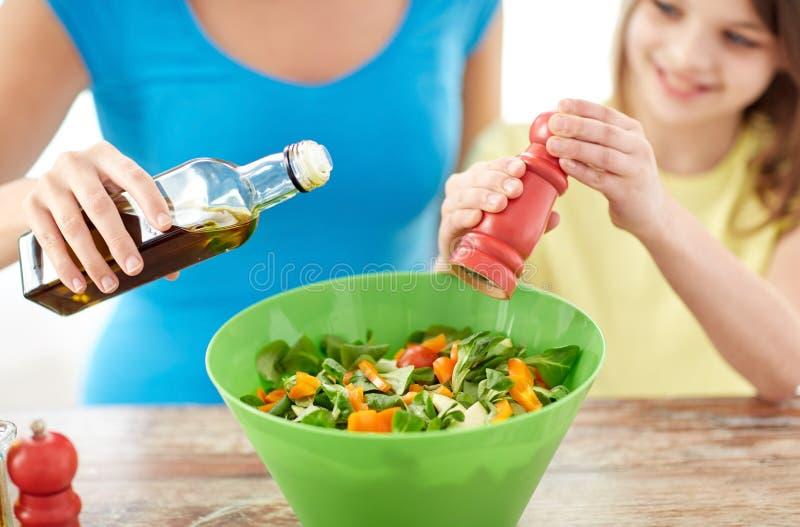 Feche acima da família feliz que cozinha a salada na cozinha imagens de stock
