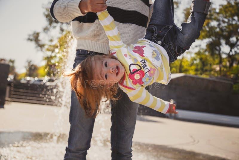Feche acima da família loving alegre feliz, mãe e a filha pequena que joga no parque ao lado da fonte, mãe nova está guardando fotos de stock royalty free
