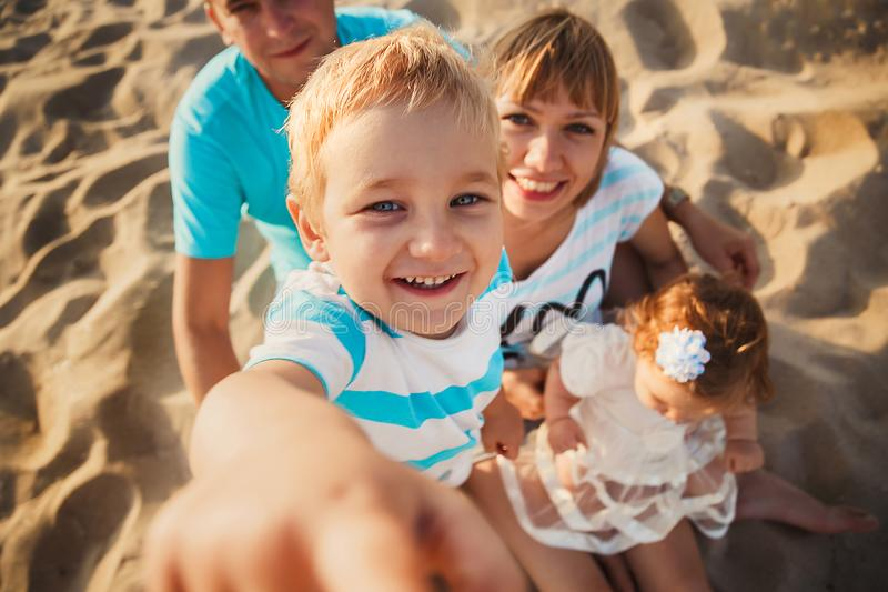 Feche acima da família loving feliz nova com as crianças pequenas no meio, tendo o divertimento na praia junto perto do oceano, e foto de stock