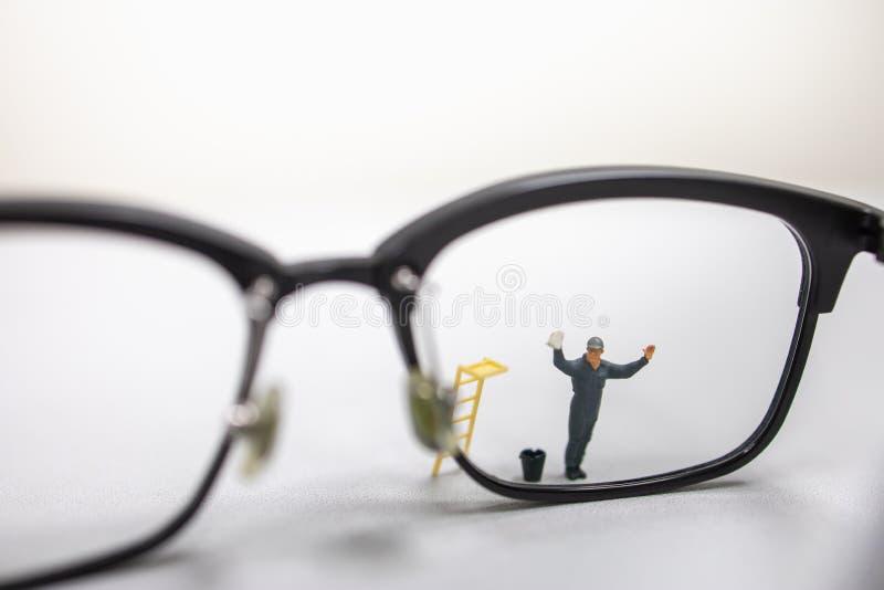 Feche acima da figura diminuta limpeza do trabalhador masculino e para limpar vidros de leitura sujos com a cubeta e a escada imagens de stock royalty free