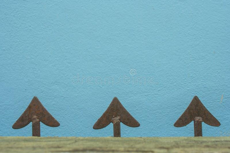 Feche acima da forma principal da seta da cerca do ferro fundido ou da cerca do metal com o muro de cimento azul no fundo fotos de stock royalty free