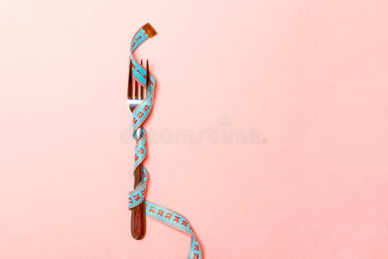 Feche acima da forquilha envolvida na fita de medição no fundo cor-de-rosa Excesso de peso e comendo demais o conceito imagens de stock