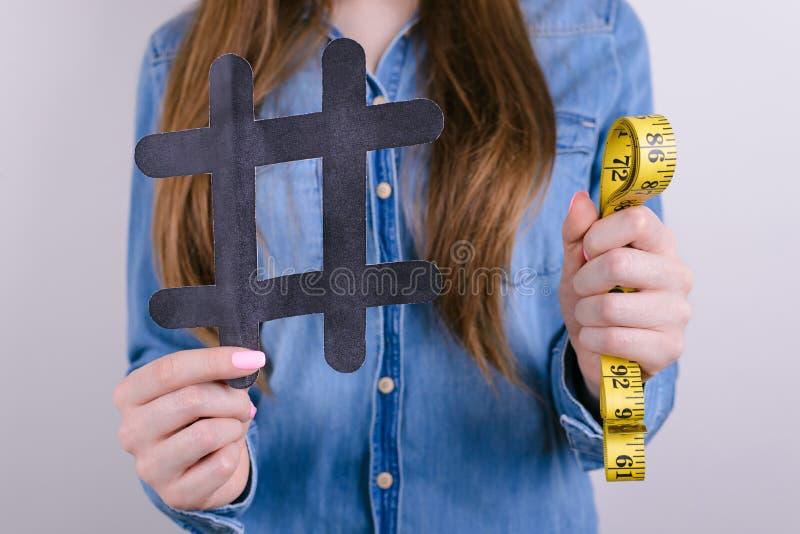 Feche acima da foto colhida da senhora satisfeita feliz que guarda mostrar o hashtag preto e do medidor o fundo cinzento amarelo  imagens de stock