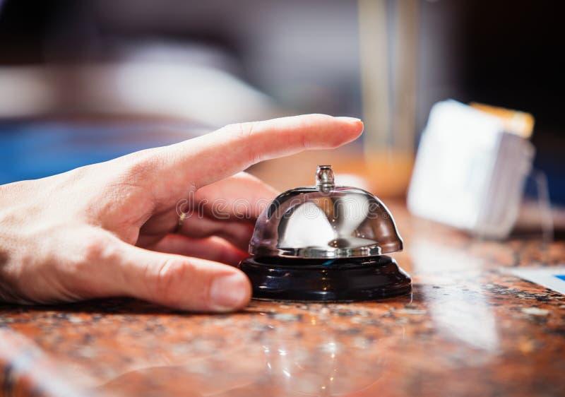 Feche acima da foto da mão que soa um sino do serviço da recepção do hotel fotos de stock