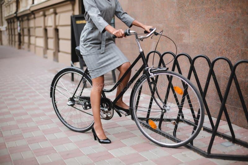 Feche acima da foto do corpo da mulher no vestido cinzento que está com bicicleta Bicicleta da equitação da jovem senhora na rua imagem de stock