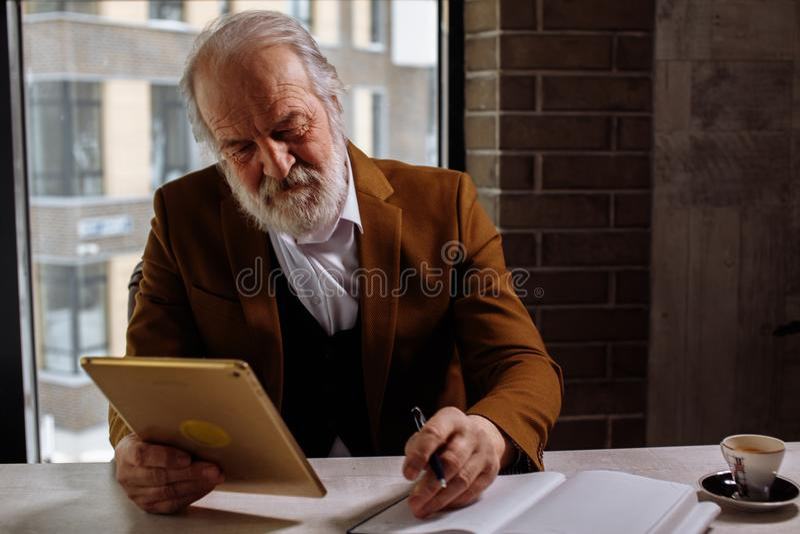 Feche acima da foto do homem atrativo idoso que guarda a tabuleta e que surfa a rede fotos de stock royalty free