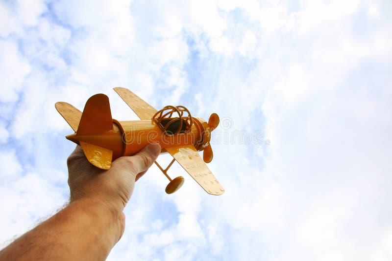 feche acima da foto do man& x27; mão de s que guarda o avião do brinquedo fotos de stock
